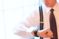 Businessman checking time on wristwatch uid
